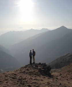 Couple standing on top of a mountain looking at the view