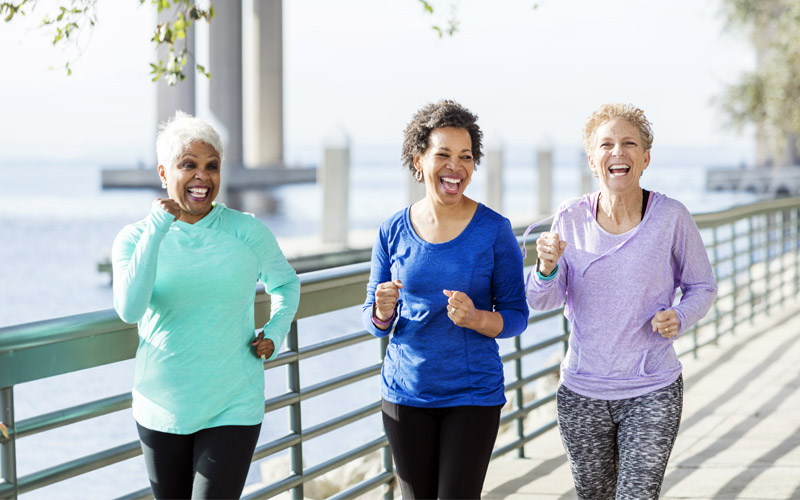 Three women in retirement jogging on a boardwalk